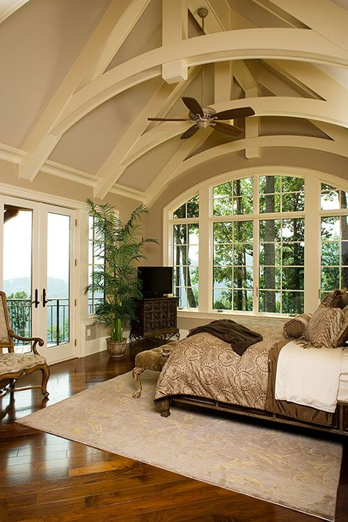 Bedroom with vaulted ceiling and large windows