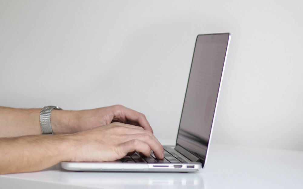 A person using a slim laptop on a clean white table.