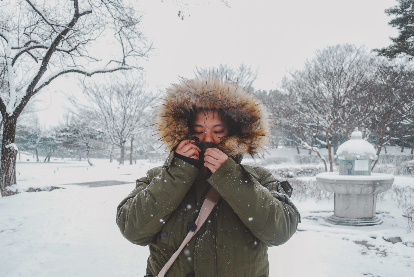 girl in winter coat with snowy back ground -what to wear in korea in the winter